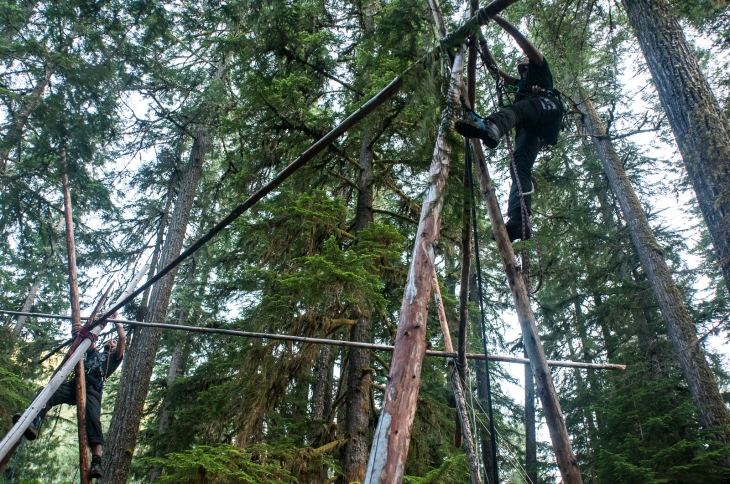 Climbers use DIY lanyards to hold themselves in position while rigging a tri-bi-mono-pod during an Earth First! Climbers Guild camp in Oregon.