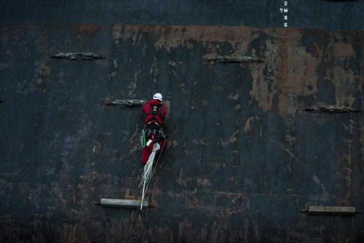 Andreas Widlund aid climbs between sacrificial zinc anodes on the pontoon of the Polar Pioneer oil rig. © Vincenzo Floramo / Greenpeace