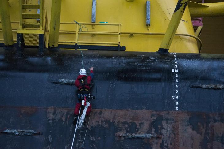 A Greenpeace climbers uses a long lanyard to aid in a final move as they finish climbing the pontoon section of the Polar Pioneer oil rig. © Vincenzo Floramo / Greenpeace